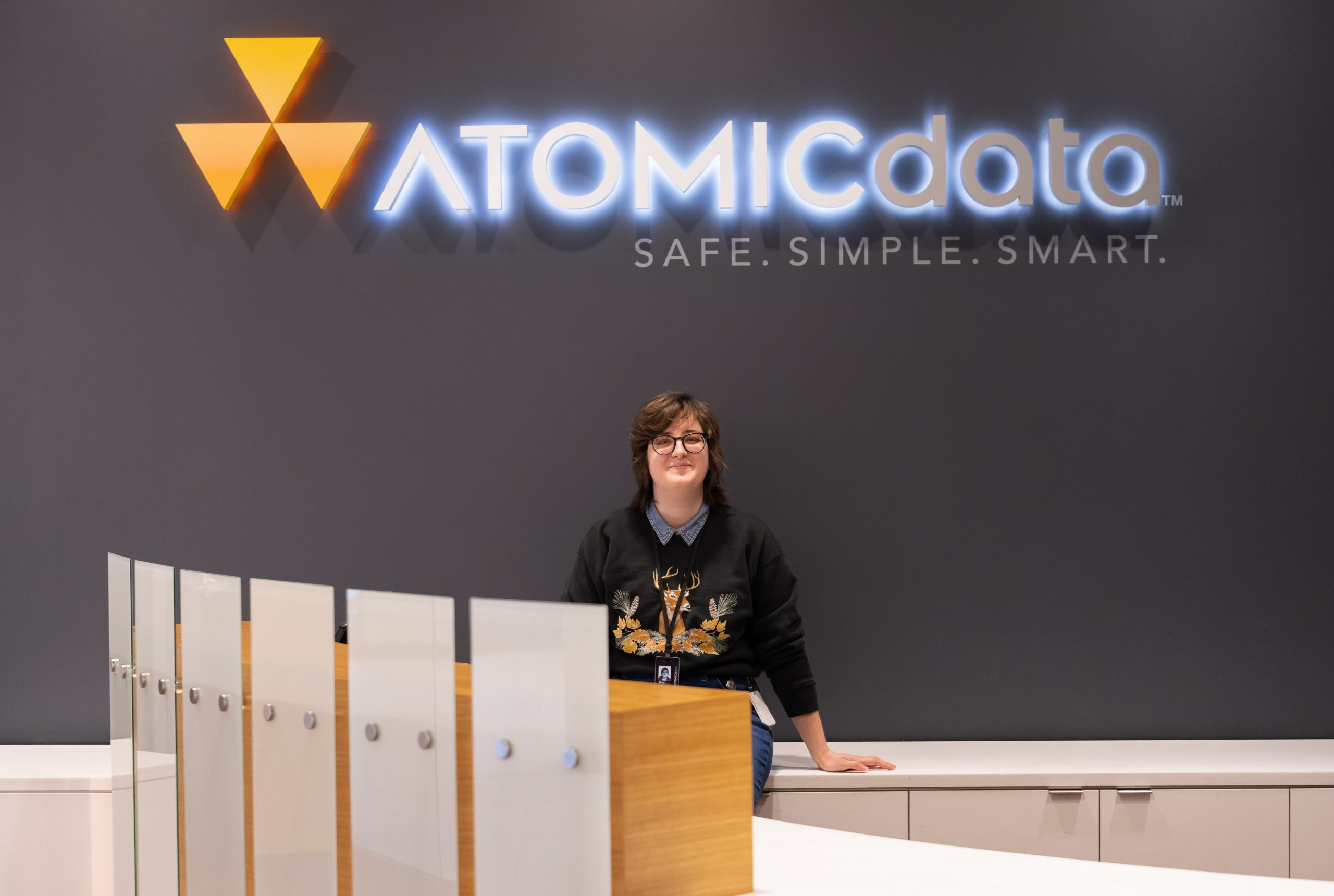 Abby Engle in front of Atomic Data sign